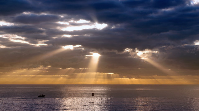 morning sun bursting through dark clouds over the sea