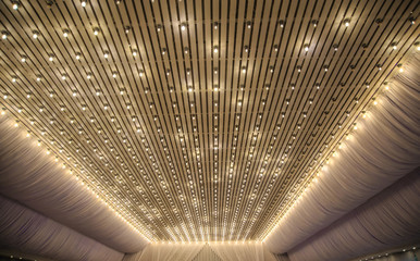close up photo of a white ceiling and a part of a wall decorated with tulle and lights in a wedding banquet hall