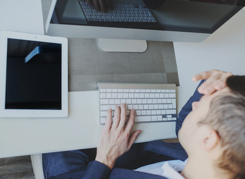 back view of a young man sitting in front of a computer monitor and thinking about a task