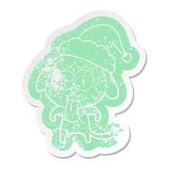 cute cartoon distressed sticker of a dog wearing santa hat