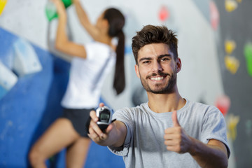 portrait of sports coach with thumbs up and showing stopwatch