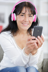 happy senior woman listening to music at home