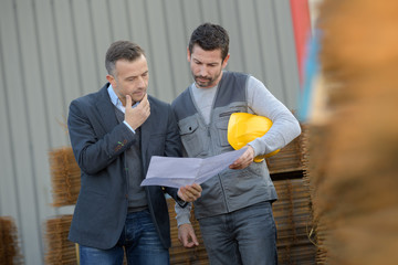 business managar and worker with factory plans outdoors