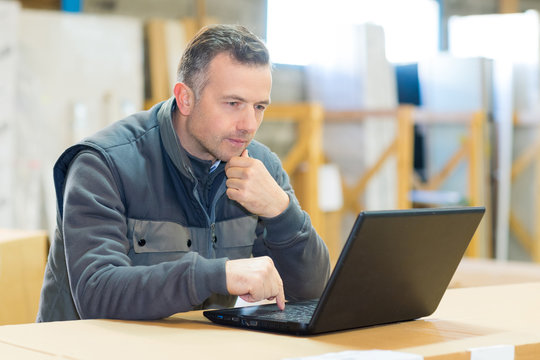 male worker looking at laptop in workshop