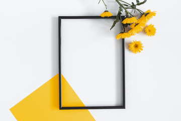 Flowers composition. Yellow flowers, photo frame on pastel gray background. Spring, summer concept. Flat lay, top view, copy space