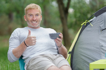 man holding cup outside tent