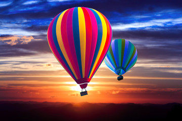 Two hot air balloon soar into the sky at sunrise