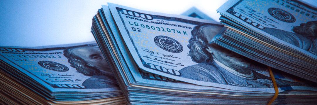 Banknotes of dollars in packs. Dark blue light.