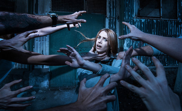 Horror. Many zombie hands are drawn to a scared girl