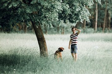 young man with his dog standing near a tree in the Park.