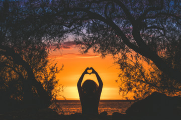 Silhouette image of a young woman making heart with hands on a beautiful summer evening Back view of a girl fingers like hearts sunset in background and branches that frame Enjoyable romance feelings