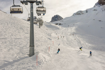 People skiing and going up the mountain by chairlift at Engelberg on the Swiss alps