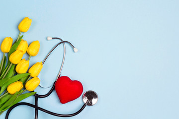 Bunch of yellow tulips with stethoscope and heart on blue background. National Doctor's day. Happy nurse day.