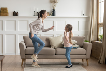 Happy mom and little kid daughter laughing dancing at home