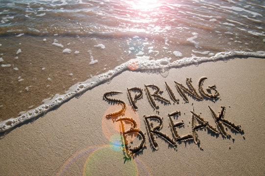 Spring Break message handwritten on the smooth sand of an empty beach with lens flare reflecting off an oncoming wave