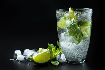 Clear shiny glass filled with ice and delicious Mojito cocktail with lime and mint composed on black background