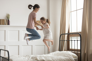 Happy mom and kid girl holding hands jumping on bed