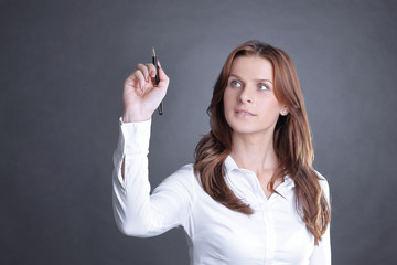 young business woman showing with pencil on the virtual point.
