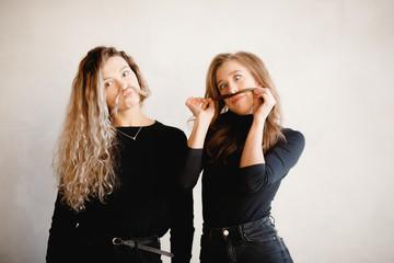 Girlfriends girls laugh, make mustache from hair on gray concrete background. Concept Sisterhood