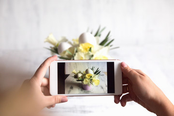hands with the phone take pictures of flowers