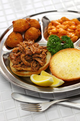 North Carolina barbecue plate ; pulled pork, hush puppies, baked beans and coleslaw