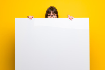 Woman with glasses over yellow wall holding a placard for insert a concept