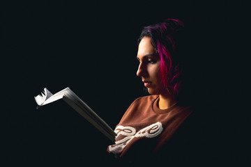 Portrait of young woman reading a book on black background low key Wall mural
