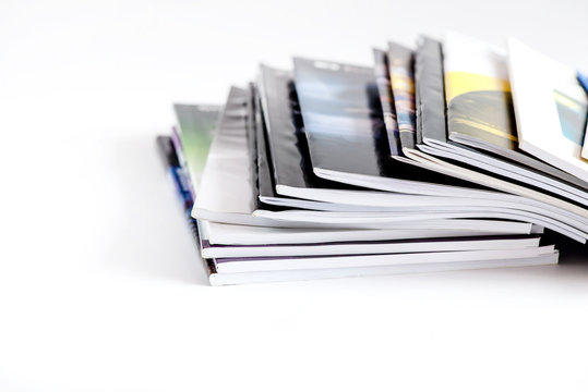 Pile of advertising magazines on a white background.