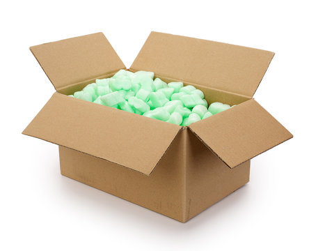 Brown corrugated cardboard moving box, filled with green styrofoam pellets or packing peanuts on white background. Contains clipping path.