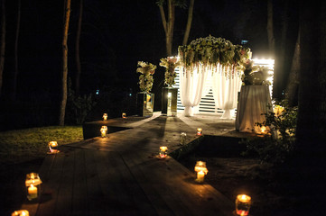 wedding arch decorated with flower compositions and curtains at night; a path with candles that goest to it