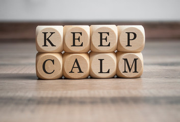 Cubes dice with keep calm on wooden background