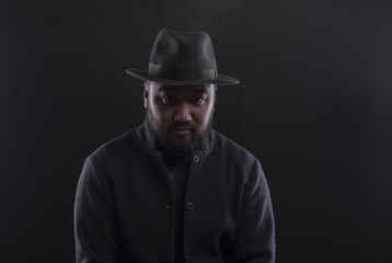 studio vintage portrait of a bearded man in a hat on a black background