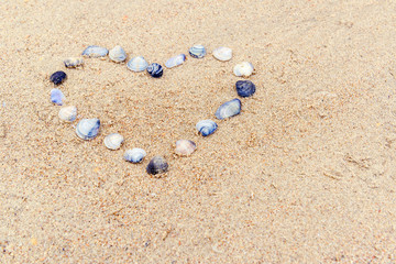 Heart built of sea shells on the sand