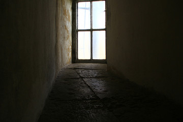 An ancient window at the end of a stone corridor