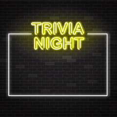 Trivia night yellow neon sign in white frame on dark brick wall background with copy space.