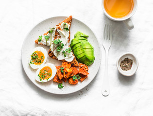 Cream cheese toast, avocado, boiled egg, baked sweet potatoes - delicious healthy breakfast or snack on a light background, top view