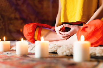 Close-up of woman's hand in yoga lotus pose meditating in a crafting room with candles