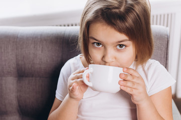 Cheerful cute adorable girl drinking milk in a cup at home