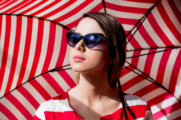 woman in sunglasses with red striped umbrella