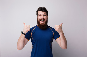 Happy funny bearded man showl like sign thumbs up and good like, on white wall background