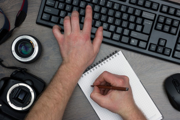 The journalist is working on an article in the office at the computer. Top view of the table with a keyboard, mouse, reflex camera and lens.