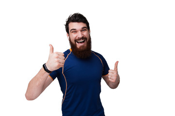 Photo of bearded man dressed in sport tshirt, rising htumbs up and smiling broadly, over white wall background