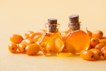 Two small bottles with Sea buckthorn oil, sea buckthorn berries on a yellow background.