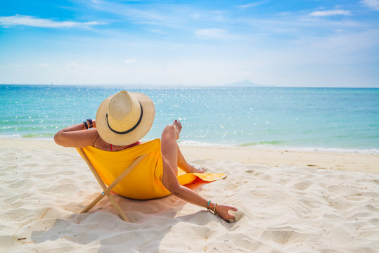 Woman enjoying her holidays on a transat at the tropical beach