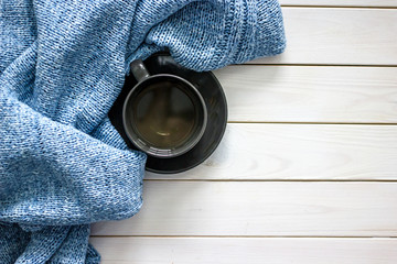 A blue knit sweater and a dark cup of coffee on a saucer in the corner of a white wooden background. Flat lay, top view, copy space