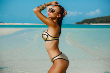 Outdoor fashion photo of a gorgeous sexy woman in a luxury gold bikini, perfect dark tanned leather, accessories and sunglasses. Tropical island trip