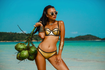 Fashion outdoor photo gorgeous sexy woman in a luxurious gold bikini, perfect dark tanned skin, in the hands of a bunch of coconuts. Tropical island trip