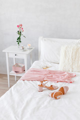 Elegant long pink dress, heeled sandals and perfume lying on the bed. Girl choosing outfit. Female modern stylish and cozy bedroom. Bed with white linen, bedside table, vase with flowers, candle.