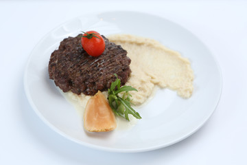 fried meat cutlet on a plate, with celery puree, garnished with tomato cherry and sour apples, isolated