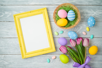 Easter holiday background with easter eggs in basket, photo frame and tulip flowers on wooden table.